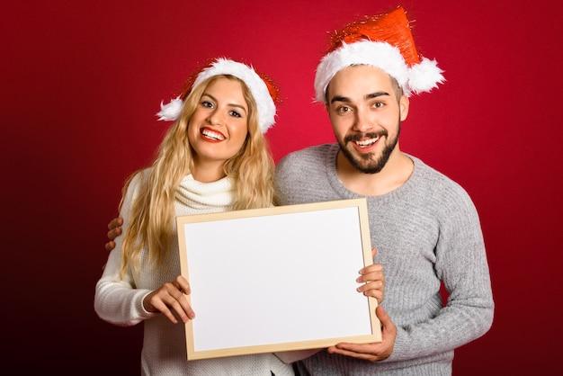 Couple Avec Un Chapeau De Père Noël Tenant Un Tableau Blanc Sur Fond Rouge Photo gratuit