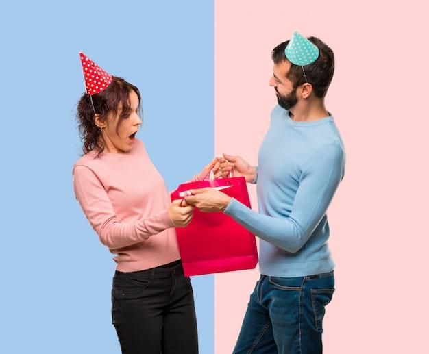 Couple avec des chapeaux d'anniversaire et des sacs à provisions sur fond rose et bleu Photo Premium
