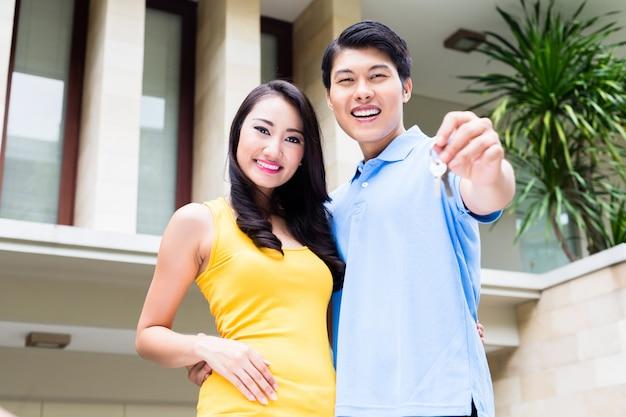 Couple chinois montrant les clés de leur nouvelle maison Photo Premium