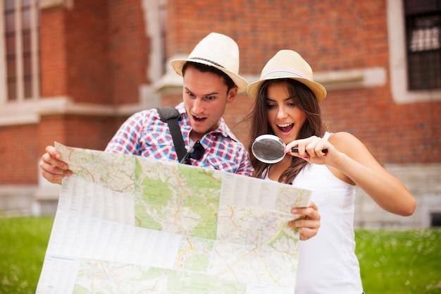 Couple Choqué Regardant La Carte à La Loupe Photo gratuit
