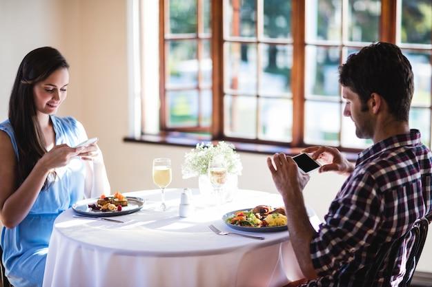 Couple en cliquant sur la photo d'un aliment sur une assiette Photo Premium