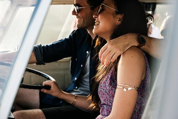 Couple conduisant une voiture voyageant sur la route ensemble Photo Premium