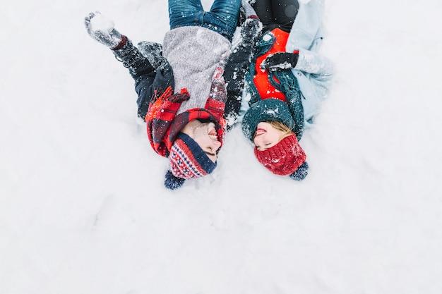 Couple de contenu allongé sur la neige Photo gratuit