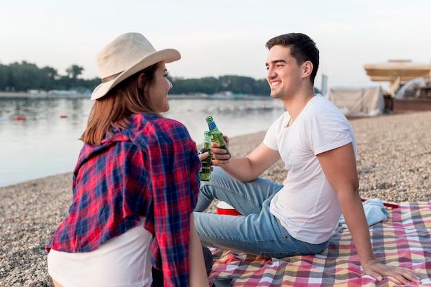 Couple sur le côté grillage sur une couverture de pique-nique Photo gratuit