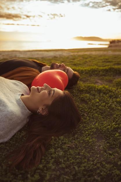 Couple Couché Sur L'herbe Avec Ballon Coeur Rouge Photo gratuit