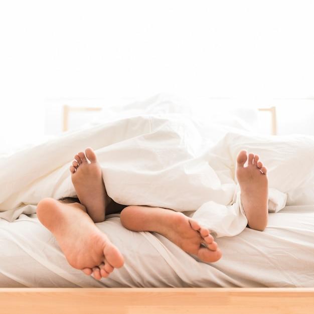 Couple couché pieds nus sur le lit Photo gratuit