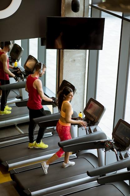 Couple courir sur des tapis de course dans le gymnase Photo Premium
