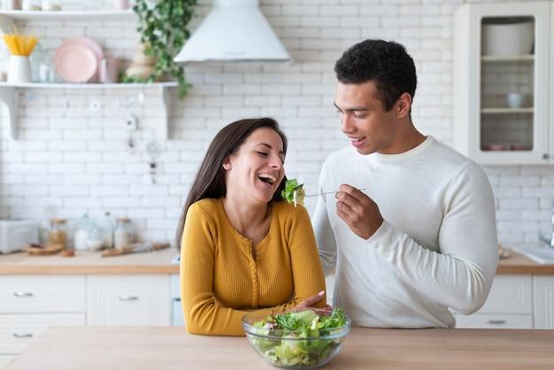 Couple, cuisine, manger, salade Photo gratuit