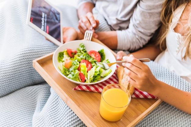 Couple de cultures appréciant la salade en regardant la série télévisée Photo gratuit
