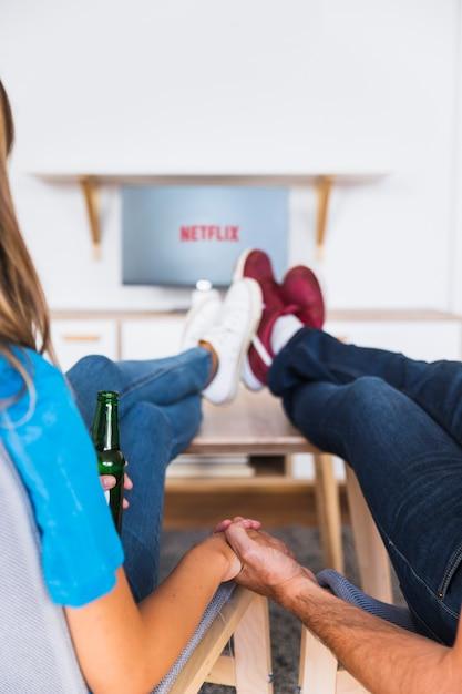 Couple de cultures avec de la bière en profitant des émissions de télévision Photo gratuit