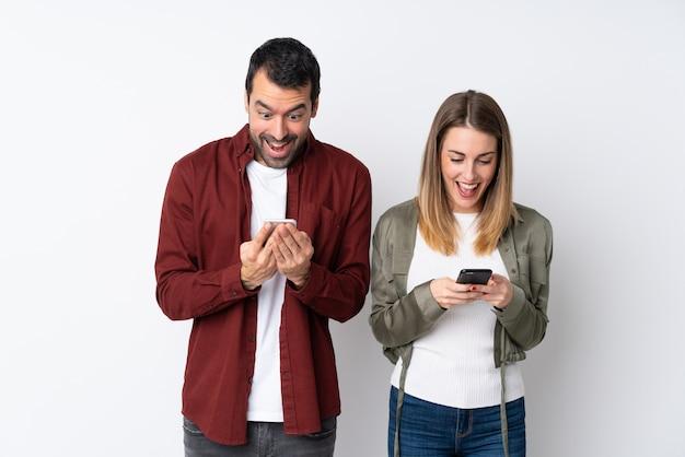 Couple Dans La Saint-valentin Sur Un Mur Isolé Surpris Et En Envoyant Un Message Ou Un E-mail Avec Le Mobile Photo Premium