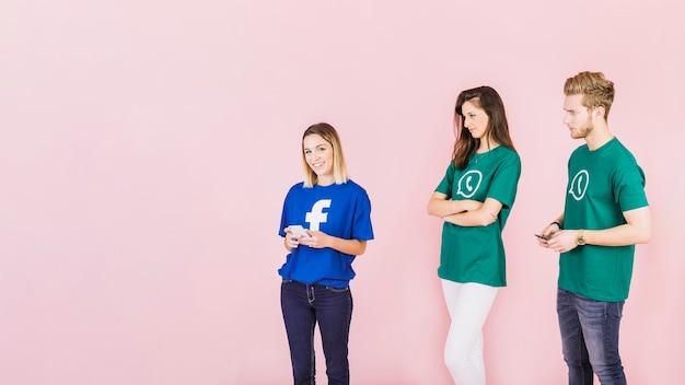 Couple dans un t-shirt whatsapp regardant une femme heureuse portant facebook top Photo gratuit
