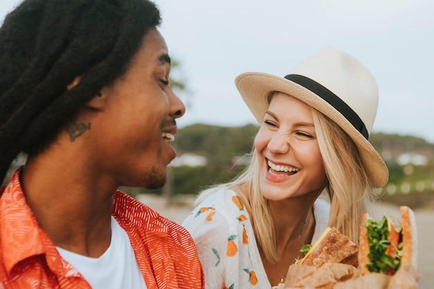 Couple datant et mangeant des sandwichs lors d'un pique-nique à la plage Photo Premium
