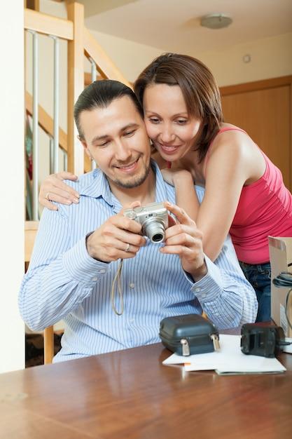 Couple déballage d'un nouvel appareil photo numérique compact Photo gratuit