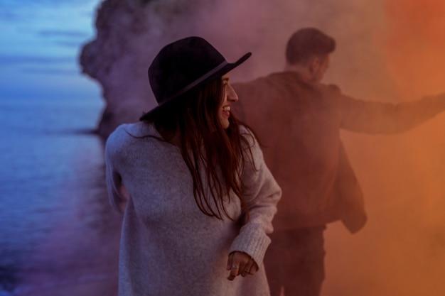 Couple debout en fumée au bord de la mer Photo gratuit