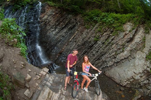 Couple debout près d'une chute d'eau près de leurs vélos dans la forêt Photo Premium