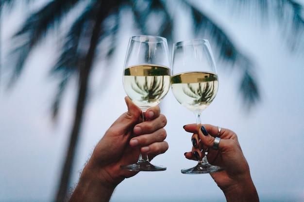 Couple en dégustant un verre de vin au bord de la plage Photo gratuit