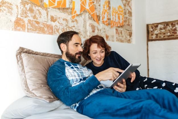 Couple Détendu à La Maison Au Lit Sur Le Téléphone Mobile Et La Tablette Photo Premium