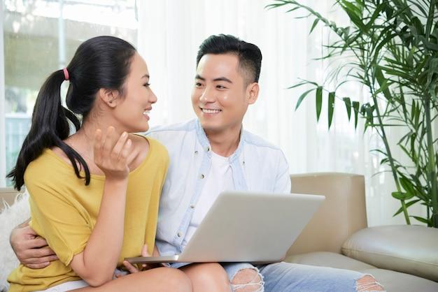Couple De Détente à L'aide D'un Ordinateur Portable Sur Un Canapé Photo gratuit