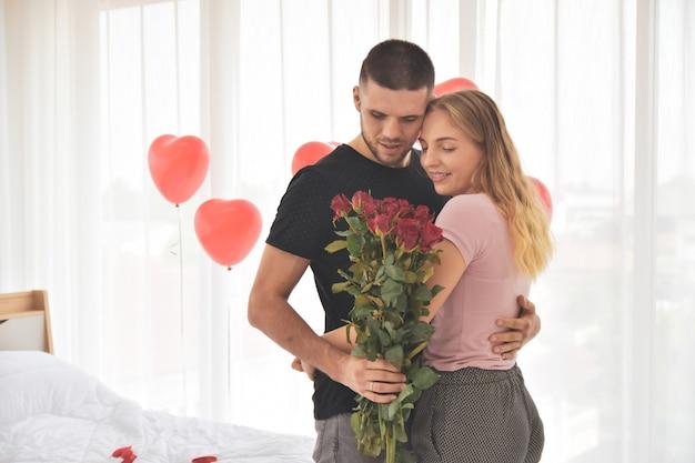 Couple, Donner, Fleur Rose, Dans, Chambre à Coucher, Bonheur, Dans, Saint Valentin, Foyer Sélectif Photo Premium