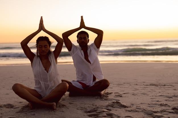 Couple effectuant le yoga ensemble sur la plage Photo gratuit