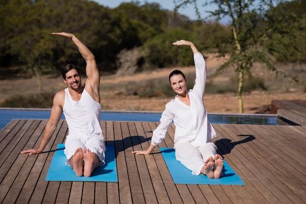 Couple Effectuant Le Yoga En Vacances De Safari Photo gratuit