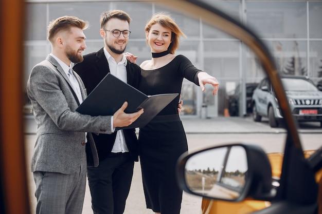 Couple élégant dans un salon de l'automobile Photo gratuit