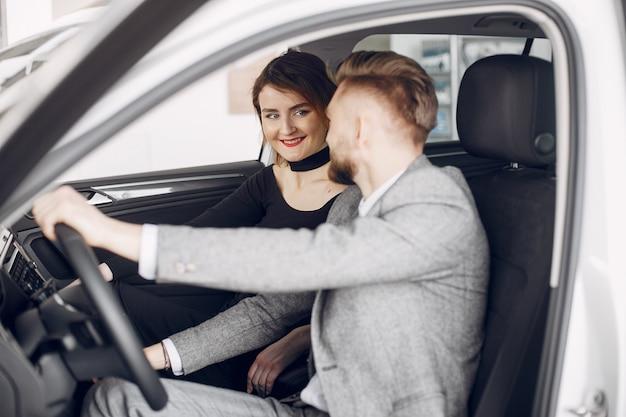 Couple élégant et élégant dans un salon de l'automobile Photo gratuit
