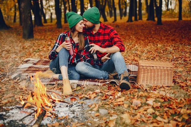 Couple élégant passe du temps dans un parc en automne Photo gratuit