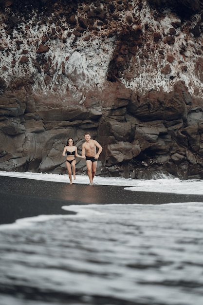 Couple élégant Sur Une Plage Près Des Rochers Photo gratuit