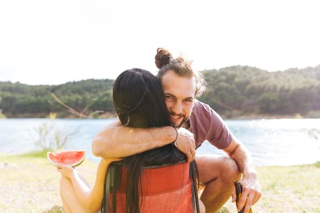 Couple embrassant au bord de la rivière Photo gratuit