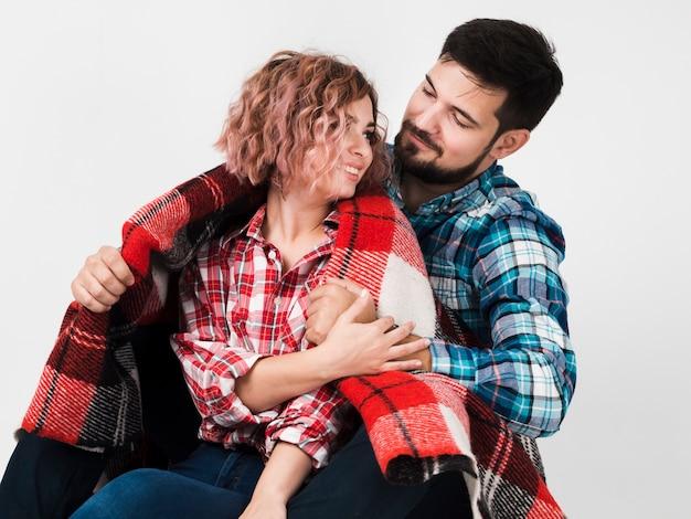 Couple embrassé avec une couverture pour la saint-valentin Photo gratuit