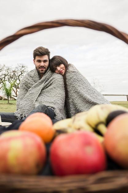 Couple enveloppé dans une couverture, assis devant un panier de fruits Photo gratuit