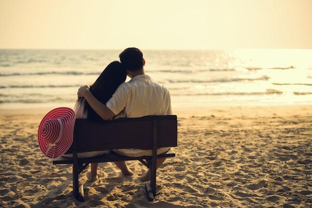 Le Couple Est Assis Près De La Plage Le Soir, Regardant Le Coucher Du Soleil. Photo Premium