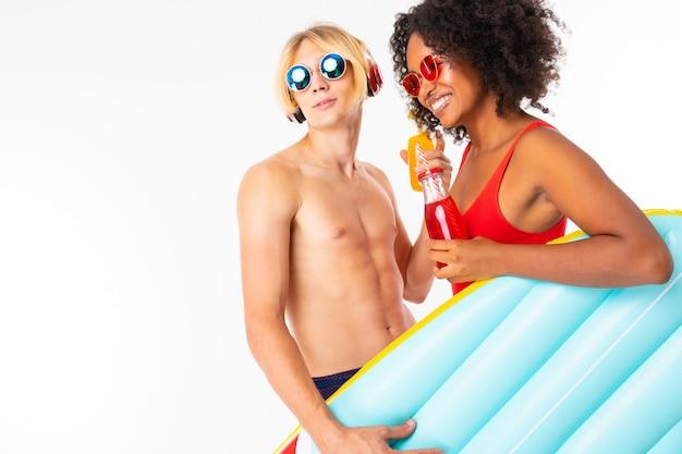 Couple Européen Heureux Guy Et Fille Africaine En Maillot De Bain Avec Des Lunettes Regarder De Côté Sur Le Mur Blanc Photo Premium