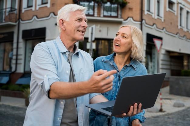 Couple à L'extérieur Dans La Ville Tout En Tenant Un Ordinateur Portable Photo gratuit