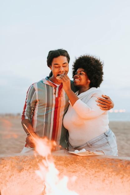 Couple, faire griller des guimauves sur un feu de joie Photo Premium