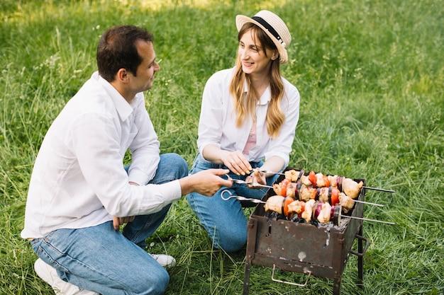 Couple faisant un barbecue dans la nature Photo gratuit