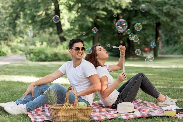 Couple faisant des bulles assis dos à dos Photo gratuit