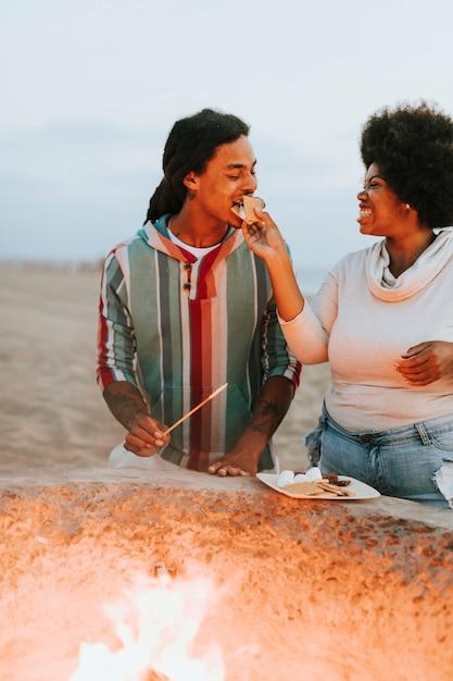 Couple faisant s'mores à la plage Photo Premium