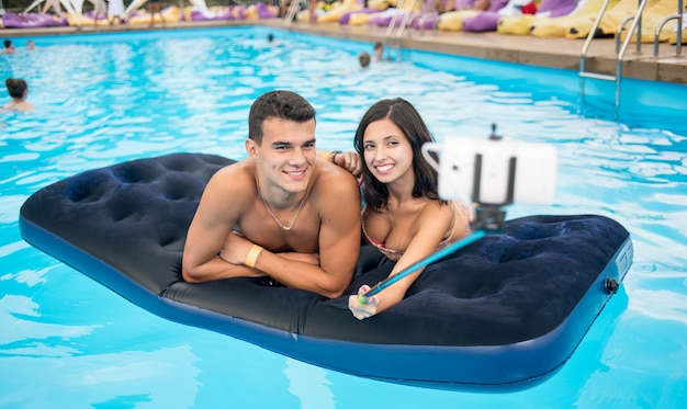 Couple faisant selfie photo sur un matelas dans la piscine Photo Premium