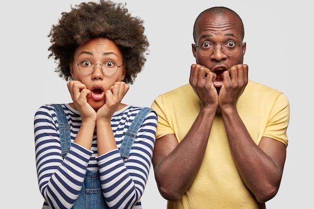 Un Couple De Famille Formidable Garde Les Mains Sous Le Menton, Regarde Avec Des Expressions Effrayées, Effrayé Par Un Terrible Accident Photo gratuit