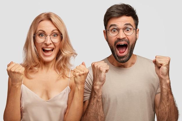 Un Couple De Famille Joyeux Reçoit De Bonnes Nouvelles Le Matin, Serre Les Poings, S'exclame De Bonheur Photo gratuit