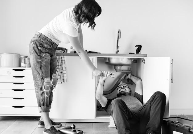 Couple fixant un évier de cuisine Photo gratuit