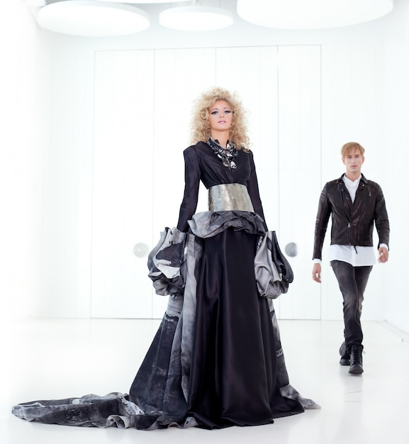 Couple futuriste rétro de haute couture noire dans une salle blanche moderne avec une inspiration de vampire Photo Premium