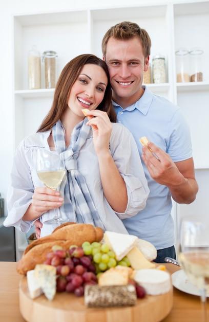 Couple gai, boire du vin blanc et manger du fromage Photo Premium