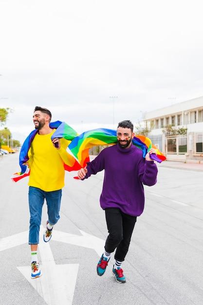 Couple gay courant le long de la route tenant des drapeaux lgbt derrière le dos Photo gratuit