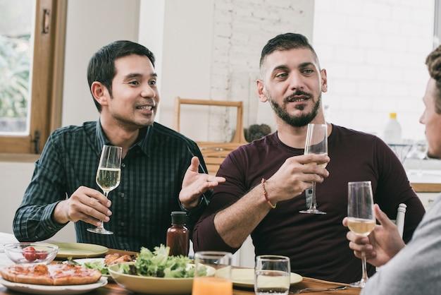 Couple gay interracial faisant la fête boire et manger à la maison Photo Premium