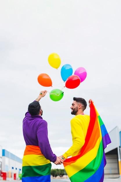 Couple gay libérant des ballons arc-en-ciel dans le ciel Photo gratuit