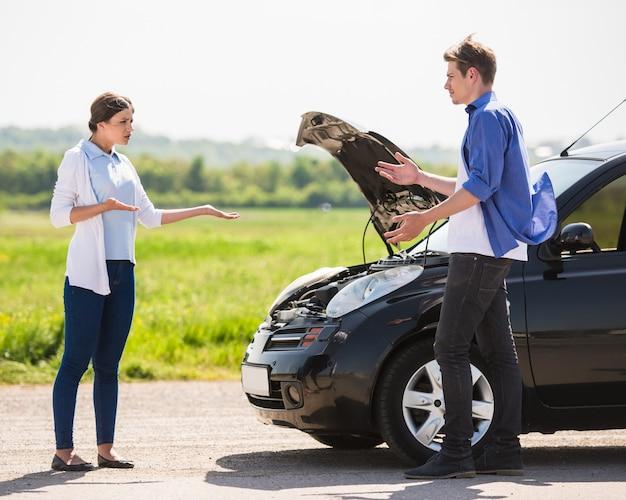 Couple habillé décontracté ayant une querelle près d'une voiture cassée. Photo Premium